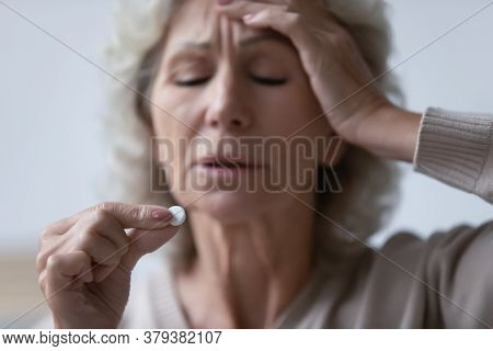 Mature Woman Touch Forehead Suffers From Headache Holding Painkiller Drug