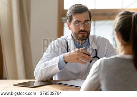 Focused Male General Practitioner Consulting Young Woman.