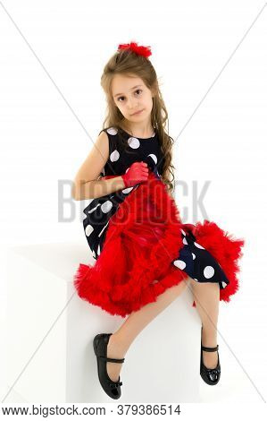 Portrait Of A Beautiful Girl In A Retro Style Dress Sitting On A White Cube, A Charming Girl In A Po