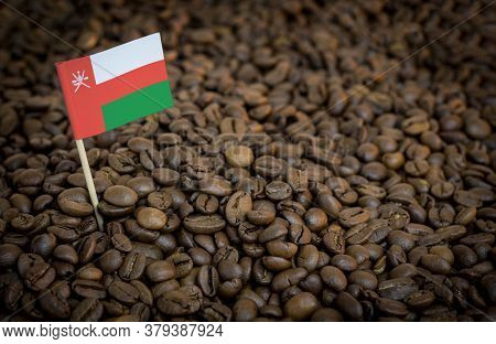 Oman Flag Sticking In Roasted Coffee Beans. The Concept Of Export And Import Of Coffee