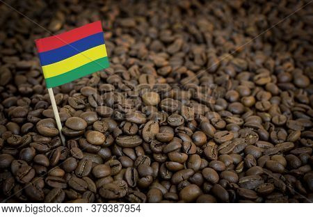 Mauritius Flag Sticking In Roasted Coffee Beans. The Concept Of Export And Import Of Coffee
