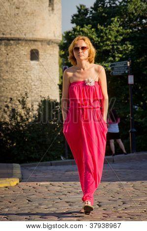 attraktive Mädchen im roten Kleid über eine Stadtstraße