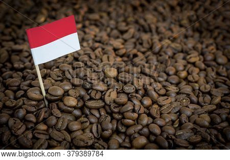 Monaco Flag Sticking In Roasted Coffee Beans. The Concept Of Export And Import Of Coffee