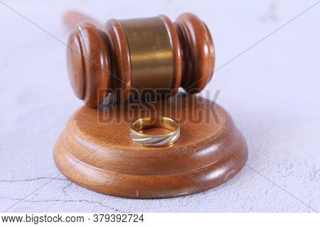 Close Up Of Ring And Gavel On Wooden Table