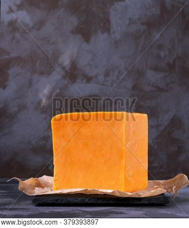 Red Cheddar Cheese Block Against The Grey Background