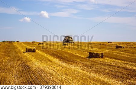 A Tractor Uses A Trailed Bale Machine To Collect Straw In The Field And Make Round Large Bales. Agri