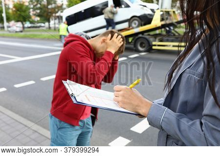 Insurance Agent Fills Out Insurance After Car Accident Driver Is Standing Next To Him And Holding Hi