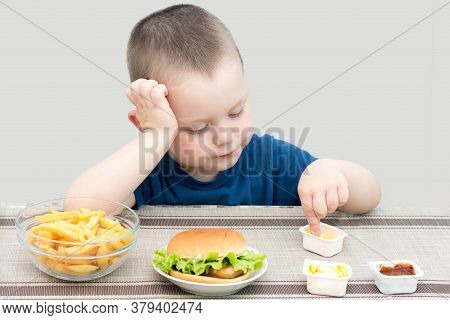 The Boy Sits And Eats Fast Food, Not Looking At The Camera, Concentrating On Eating French Fries.hor