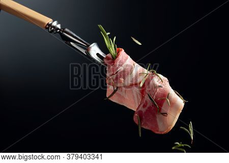 Bacon Slices And Rosemary On A Fork. Smoked Bacon On A Black Background With Copy Space.