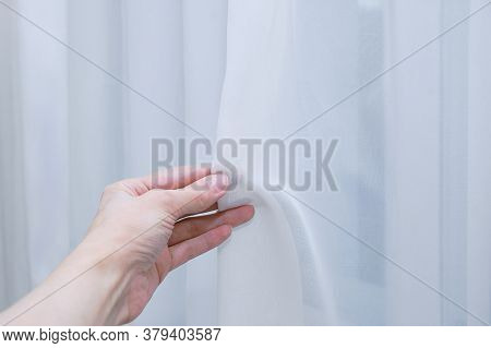 White Translucent Curtain Tulle In The Hand Of A Caucasian Woman.
