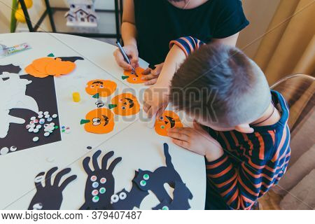 Young Mother With Toddler Son Making Craft Pumpkins For Halloween Holiday