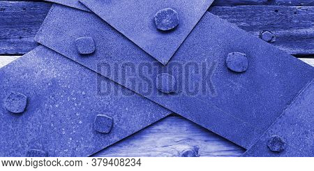 Closeup Texture Of Rusty Iron Sheets Or Slats Bolted To Aged Wooden Planks In In Blue And Purple Ton