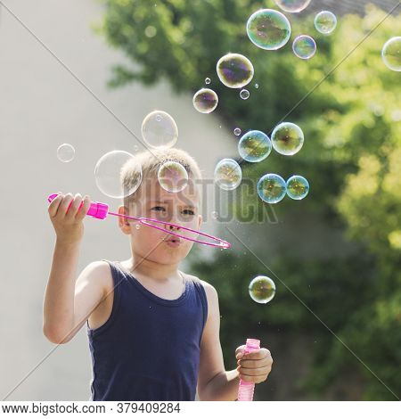 Cute Six Years Old Blond Hair Boy Is Blowing Soap Bubbles Outdoors.