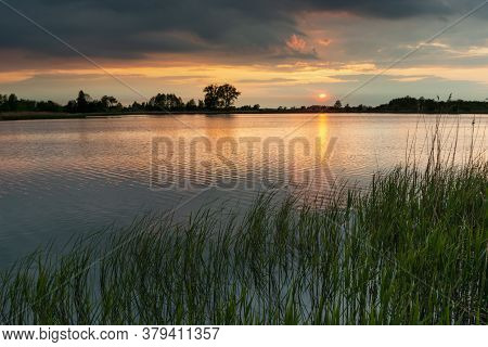 Sunset And Dark Clouds Over A Peaceful Lake With Green Reeds