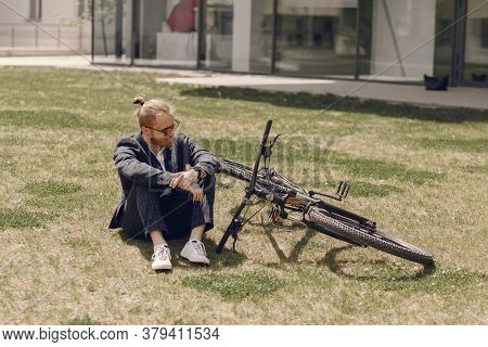 Businessman With Bicycle In A Summer City