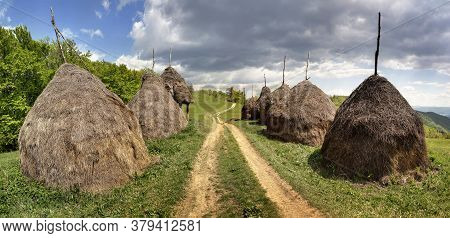 Rows Of Haystacks With Path In Banat, Romania