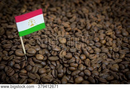 Tajikistan Flag Sticking In Roasted Coffee Beans. The Concept Of Export And Import Of Coffee