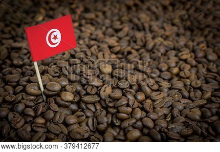 Tunisia Flag Sticking In Roasted Coffee Beans. The Concept Of Export And Import Of Coffee