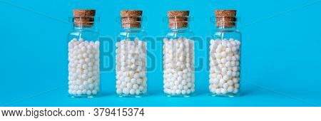 Banner Image Of Homeopathic Globules In Glass Bottles On Pastel Blue Background. Alternative Homeopa