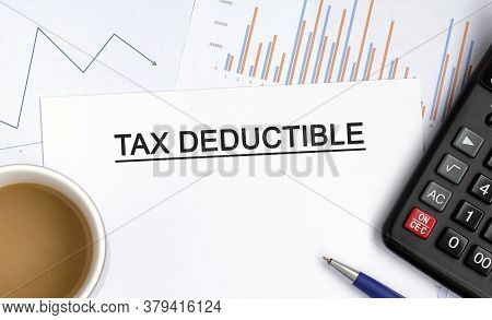 Tax Deductible Document With Graphs, Diagrams And Calculator And A Cup Of Fragrant Coffee