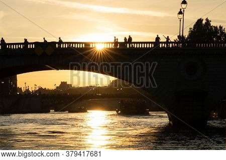 Silhouette Of Bridge Named Pont Au Change, With People Waving Hand Over Seine River At Sunset In Par