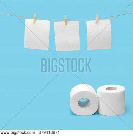Toilet Paper Hangs To Dry On A Clothesline. Toilet Paper Rolls On A Blue Background. The Concept Of