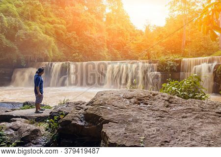 Travel And Freedom. Young Asian Man  With Hand Up Enjoying Tropical Waterfall View. Waterfall In The