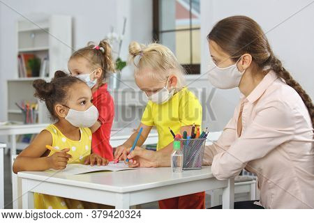 A Teacher And Children With A Mask On Their Face At School In The Classroom After Covid19 Quarantine