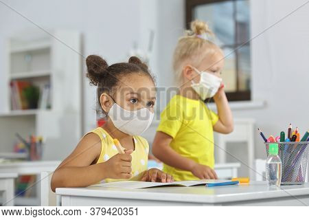 A Dark-skinned Girl In A Medical Mask For Protection From Infection In A Yellow Dress Listens Attent