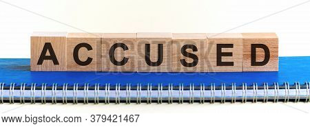 Accused - A Word Made Of Wooden Blocks With Black Letters, A Row Of Blocks Is Located On A Blue Note