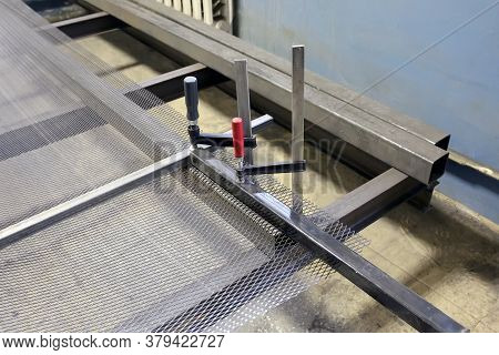 An Iron Mesh Netting Lies In A Locksmith Workshop, Preparation For Cutting With An Iron Circle.