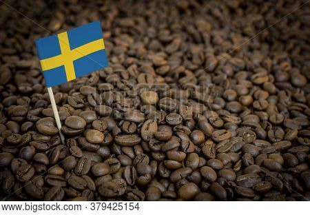 Sweden Flag Sticking In Roasted Coffee Beans. The Concept Of Export And Import Of Coffee