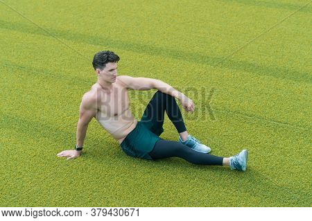 Muscular Guy Makes Sit On Grass. Shirtless Sportsman Resting After Workout. Guy Sitting On Grass. Pl