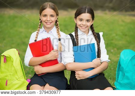 Small Girls With Books And Backpacks. Children Hold Notebook For Making Notes. Happy Childhood. Back