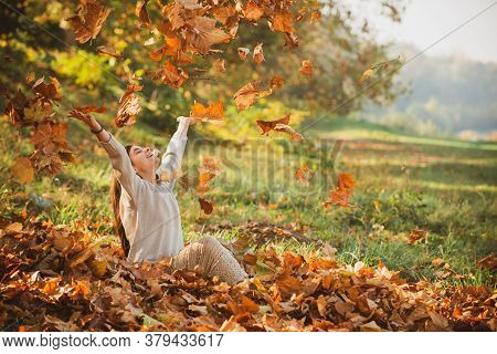 Autumn Leaves Falling On Happy Young Woman In Forest. The Colors And Mood Of Autumn. Beautiful Young