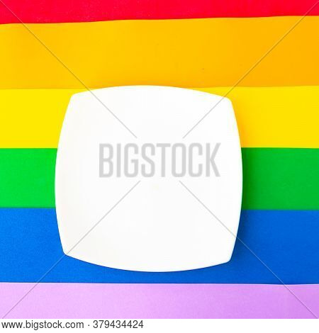 White Mockup Plate On Lgbtq Colors Flag, Top View, Copy Space For The Text