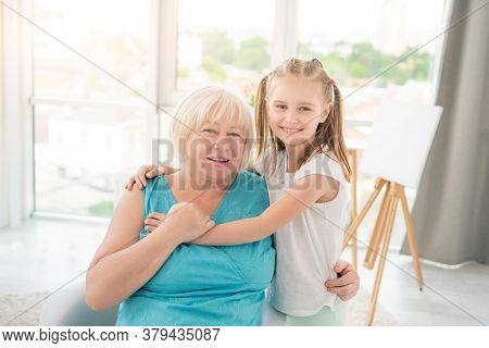 Cute little girl embracing smiling granny in light room