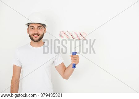 Portrait of smiling handsome young male decorator with stubble wearing hardhat holding paint roll against white wall