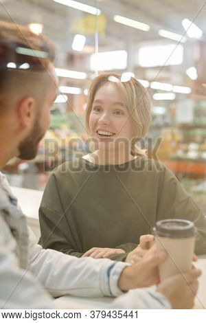 Positive young couple sitting in cafe and chatting while drinking coffee together
