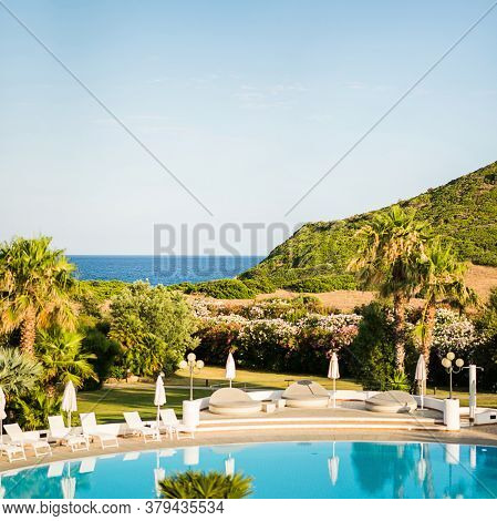 Empty Water Pool with Sunbeds with Umbrellas. Mediterranean Landscape. Luxury Panoramic View on Mediterranean Sea. Sardinia. Italy.