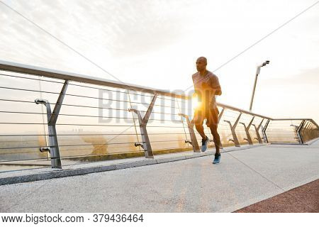 Side view of a young african man jogger exercising outdoors on a bridge