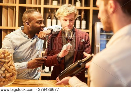 Young people having sommelier at a wine tasting or tasting in a bar