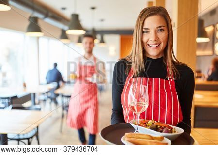 Young smiling woman serving as a waitress serves appetizers in the restaurant or bistro