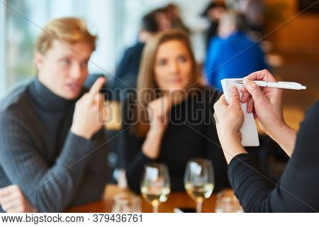 Service staff or waiter notes order from guests in the bistro or restaurant