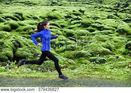 Running woman. Young female runner jogging and trail running on footpath. Woman is exercising in nature.
