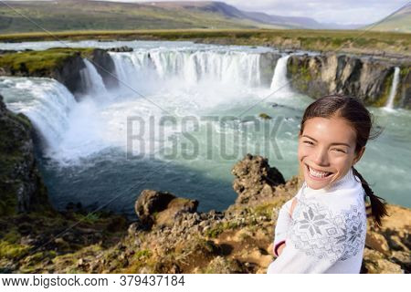 Woman portrait on travel by Godafoss waterfall on Iceland. Happy young woman tourists enjoying icelandic nature landscape visiting famous tourist destination attraction, Iceland.