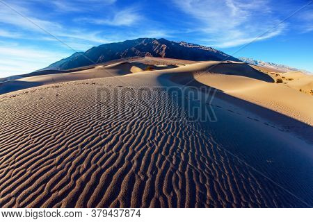 Mesquite Flat Sand Dunes is part of Death Valley in California. USA. Light sand waves from the desert wind. Magic play of light on the sand. The concept of ecological and photo tourism. Fisheye lens