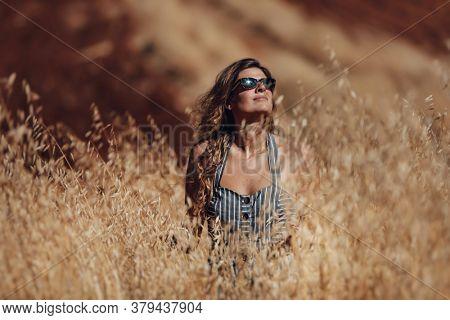 Beautiful Women Enjoying Great Summer Day on the Gold Wheat Field. Model Wearing Stylish Sunglasses, Posing Outdoors. The Beauty of Autumn.