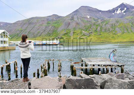Tourist on Iceland taking photo of Siglufjordur Fjord wearing icelandic sweater. Woman visiting iceland sightseeing in Siglufjordur city taking picture using phone camera. North Iceland.