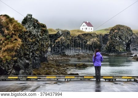 Iceland nature landscape on Arnarstapi Snaefellsnes. Travel photo of woman tourist looking at view of dramatic coast and ocean on West Iceland. From Arnarstapi harbour, Iceland.